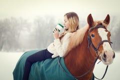 Jeune fille de cavalier détendant à cheval avec du café Image stock