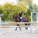 Jeune fille de cavalier de cheval sur la concurrence équestre Images stock