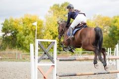 Jeune fille de cavalier sautant par-dessus barier sur son cours Photos stock