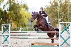 Jeune fille de cavalier sautant par-dessus barier sur son cours Images stock