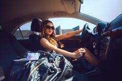 Jeune fille de Cutie dans des lunettes de soleil conduisant une nouvelle voiture avec le sac plein o Photographie stock