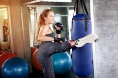 jeune fille de forme physique faisant l'exercice donnant un coup de pied le sac de sable le gymnase OE images libres de droits
