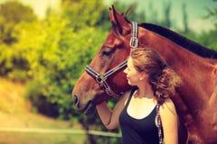 Jeune fille de jockey choyant et étreignant le cheval brun Photographie stock libre de droits