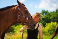 Jeune fille de jockey choyant et étreignant le cheval brun Image stock