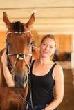 Jeune fille de jockey choyant et étreignant le cheval brun Photo stock