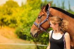 Jeune fille de jockey choyant et étreignant le cheval brun images libres de droits