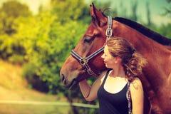Jeune fille de jockey choyant et étreignant le cheval brun Photos libres de droits