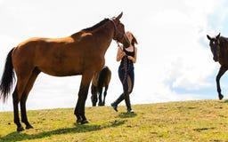 Jeune fille de jockey choyant le cheval brun Photos stock