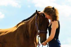 Jeune fille de jockey embrassant et étreignant le cheval brun Photos stock