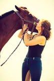 Jeune fille de jockey embrassant et étreignant le cheval brun Image stock