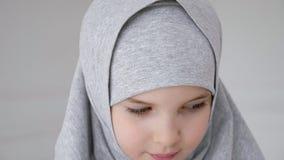 Jeune fille de l'adolescence musulmane dans le hijab regardant timidement la cam?ra et le sourire banque de vidéos