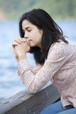 Jeune fille de l'adolescence priant tranquillement sur le pilier de lac Photos stock
