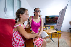 Jeune fille de la préadolescence ayant la leçon de guitare à la maison Photo libre de droits