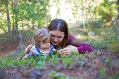 Jeune fille de mère et d'enfant en bas âge se trouvant au sol regardant vers le bas Photographie stock libre de droits