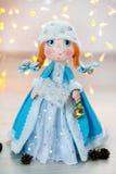 Jeune fille de neige de fille de neige de nouvelle année de jouet de cadeau sur le fond des lumières Photographie stock