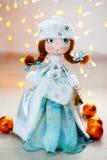 Jeune fille de neige de fille de neige de nouvelle année de jouet de cadeau sur le fond des lumières Photo libre de droits