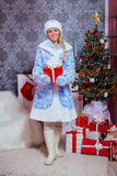 Jeune fille de neige (Snegurochka) tenant un cadeau de nouvelle année Photographie stock libre de droits