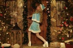 Jeune fille de neige sur le seuil de la maison décoré dans l'essai de style de Noël à la porte ouverte Image libre de droits