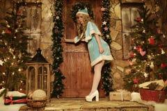 Jeune fille de neige sur le seuil de la maison décoré dans l'essai de style de Noël à la porte ouverte Photos stock