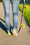 Jeune fille de planchiste marchant avec sa planche à roulettes en parc, dehors Photo stock