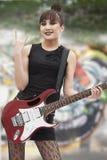 Jeune fille de punk rock donnant des klaxons de diable avec sa main et tenant la guitare Photos stock