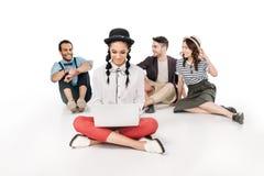 Jeune fille de sourire à l'aide de l'ordinateur portable tandis qu'amis heureux s'asseyant derrière Photographie stock