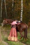 Jeune fille de sourire étreignant son cheval Photographie stock