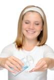 Jeune fille de sourire appliquant la lotion de nettoyage de visage Photographie stock libre de droits