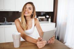 Jeune fille de sourire attirante s'asseyant à la table de dîner et tenant le comprimé Photo stock