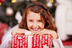 Jeune fille de sourire avec un cadeau de Noël rouge photo libre de droits