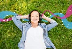 Jeune fille de sourire dans des écouteurs se trouvant sur l'herbe Photographie stock