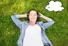 Jeune fille de sourire dans des écouteurs se trouvant sur l'herbe Photos libres de droits