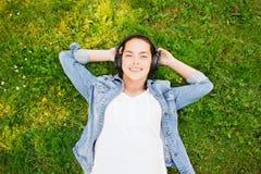 Jeune fille de sourire dans des écouteurs se trouvant sur l'herbe Image stock