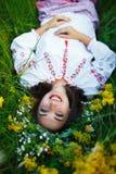 Jeune fille de sourire dans le costume ukrainien avec une guirlande sur son hea Photos stock