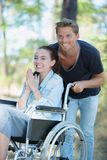Jeune fille de sourire dans le fauteuil roulant jouant avec l'ami extérieur Image libre de droits