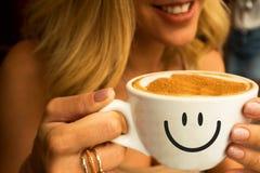 Jeune fille de sourire dans un café tenant une grande tasse de cappuccino chaud avec la conception de mousse de café du coeur là- photo stock