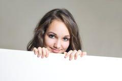 Jeune fille de sourire de brunette avec le signe blanc blanc. Photographie stock