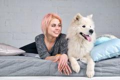 Jeune fille de sourire heureuse avec les cheveux blonds dans des vêtements à la maison o menteur Photographie stock libre de droits