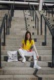 Jeune fille de sourire heureuse s'asseyant sur des escaliers photos libres de droits