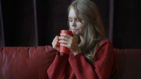 Jeune fille de sourire mignonne dans le chandail rouge appréciant son café à la maison clips vidéos