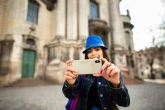 Jeune fille de sourire prenant des photos des monuments architecturaux de la vieille ville Lviv l'ukraine image stock