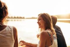 Jeune fille de sourire s'asseyant par un lac avec des amis Photographie stock libre de droits