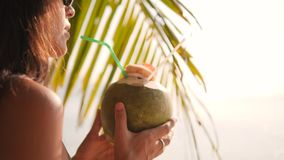 Jeune fille de touristes de hippie de métis attrayant buvant le cocktail thaïlandais frais de l'eau de noix de coco à la plage tr clips vidéos