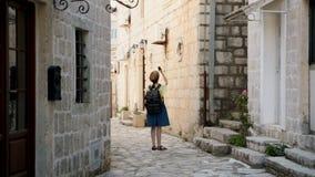 Jeune fille de voyageur de hippie voyageant chez Monténégro et regardant des points de repère de Perast Touriste assez féminin av banque de vidéos