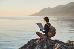 Jeune fille de voyageur s'asseyant avec la carte près de la mer au coucher du soleil, au voyage, à la hausse et au concept actif  images stock