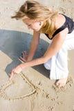 Jeune fille dessinant une forme de coeur sur le sable Images libres de droits