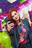 Jeune fille devant le graffiti faisant le selfie Images stock
