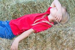 Jeune fille dormant paisiblement sur des balles de foin. Images libres de droits