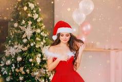 Jeune fille douce dans une robe de Santa Claus de l'écarlate de nouvelle année, une pose, un regard rouges vers le bas, clôturant photo libre de droits