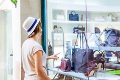 Jeune fille doutante regardant la fenêtre de boutique avec des chaussures et des sacs dans le centre commercial Client ventes Cen Photo stock